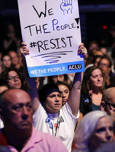 "A unidentified lady hold up signs during a meeting called ""The Resistance Training"" hosted by the American Civil Liberties Union, Saturday, March 11, 2017, in Coral Gables, Fla."