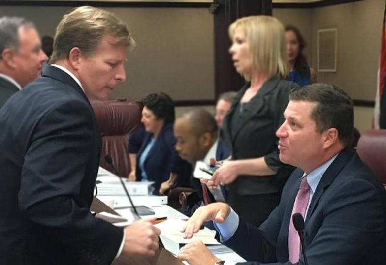 Enterprise Florida CEO Chris Hart, left, speaks to State Sen. Jeff Brandes, R-St. Petersburg, after a committee meeting on Feb. 15, 2017. Hart suddenly resigned on Monday.