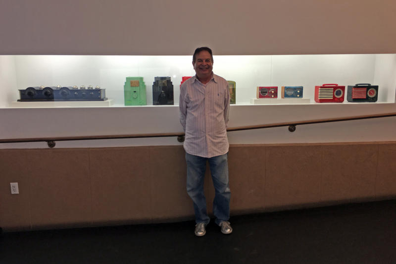 Harvey Mattel, a radio collector and enthusiast, stands in front of a selection of his radios on display for RadioFest at The Wolfsonian-FIU in South Beach.