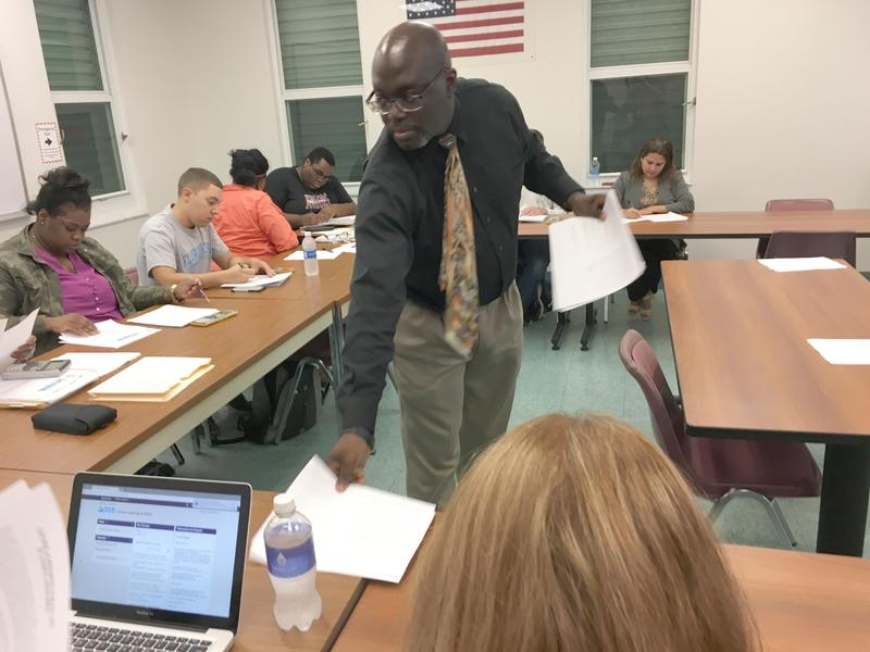 Jemal Alston, chair of business programs at Florida Keys Community College, passes out course material at the first meeting of the Financial Management course.