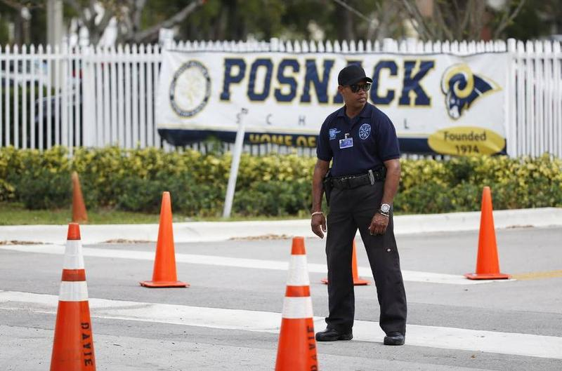 Authorities stand outside the entrance to the David Posnack Jewish Community Center and David Posnack Jewish Day School after people were evacuated because of a bomb threat, Monday, Feb. 27, 2017, in Davie, Fla.
