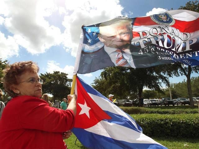 Cuban-American Emilia Garcia waves Cuban and Trump flags at a Tropical Park rally in Miami last Saturday.