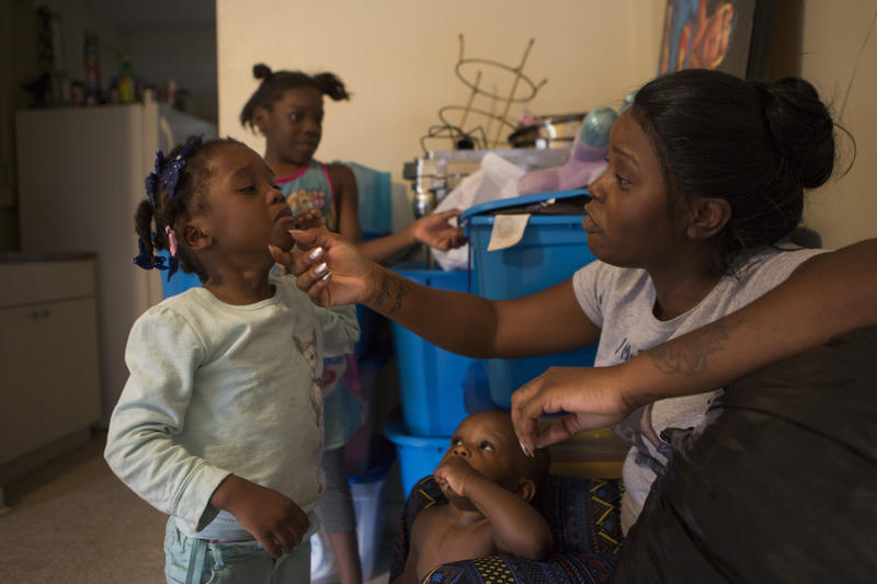 Louissita Chery tends to her daughter in the Liberty Square housing project. Chery and her family were moved from their last Miami-Dade County-owned apartment after she complained about what she believed to be a mold problem.