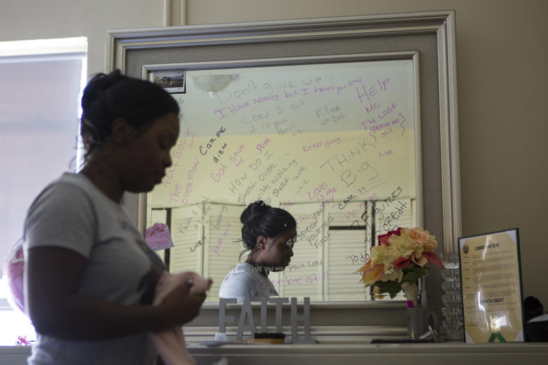 ouissita Chery writes messages to herself on a mirror inside her Liberty City apartment.