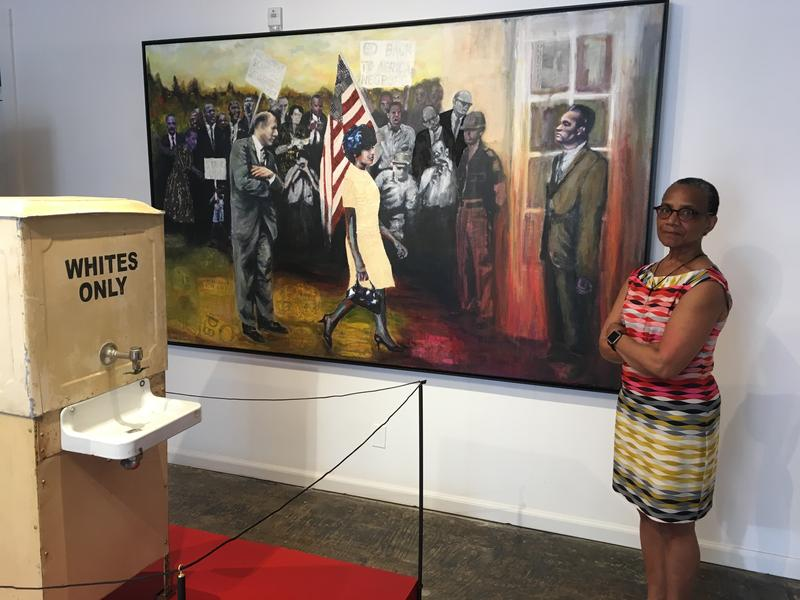 Artist Avis Collins Robinson with her painting 'Fears No Evil' and the segregation-era water cooler, both on display in The Fabric Of Soul