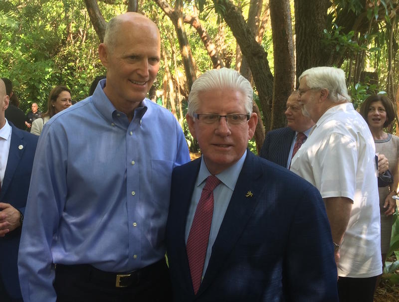 Gov. Rick Scott poses with Bill Talbert, right, of the Greater Miami Convention & Visitors Bureau, at a press conference Monday.