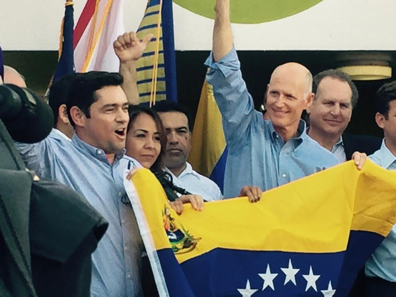 Florida Governor Rick Scott (right) holds the Venezuelan flag with opposition leader Carlos Vecchio in Doral Monday night.