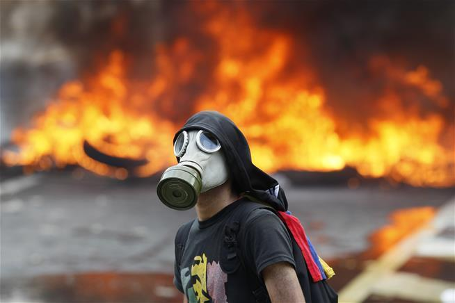 An anti-government protester wearing a tear-gas mask in front of a burning barricade in Caracas in April.