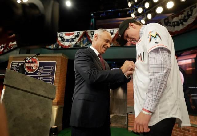 Baseball commissioner Rob Manfred, left, buttons up the jersey of Trevor Rogers, a pitcher from Carlsbad High School in Carlsbad, N.M., after being selected No. 13 by the Miami Marlins in the first round of the Major League Baseball draft, Mon., June 12