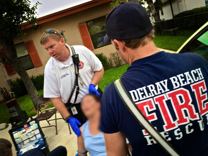 Delray Beach Fire Rescue Battalion Chief Ed Beardsley (center) and firefighter-paramedics treat a woman overdosing on heroin in Delray Beach on May 19,2017. Neighbors say a car pulled up to a stop sign, pushed the woman out and drove away.
