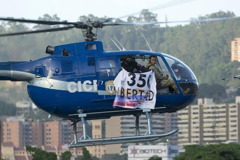 "Venezuelan police officer Oscar Perez - reportedly at the controls of this commandeered police helicopter - flying over the Caracas presidential palace Tuesday. The banner says, ""Freedom 350."""