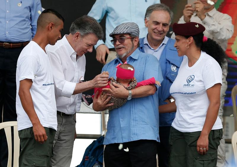Colombian President Juan Manuel Santos (second from left) at a ceremony Tuesday in Mesetas, Colombia, admires a baby born to parents of FARC guerrillas who have now disarmed. Holding the infant is FARC leader Rodrigo Londono.