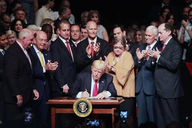 "President Trump signs his ""new deal"" with Cuba last Friday at the Manuel Artime Theater in Little Havana as Florida political leaders, Cuban-American leaders and Cuban dissidents watch."