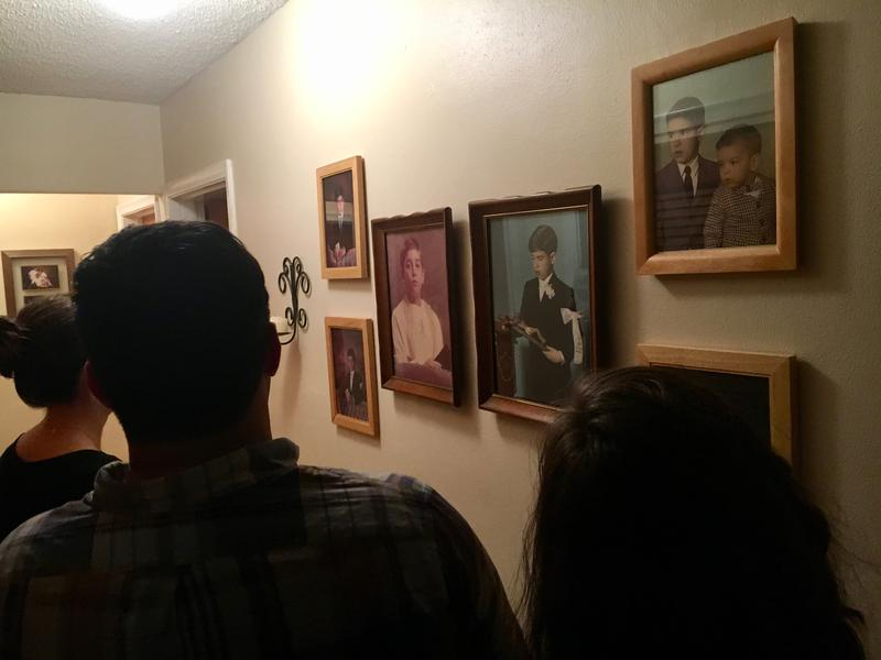 Dinner guests walk down the hall at Blanco's home, where there are photos of him and his relatives as children.