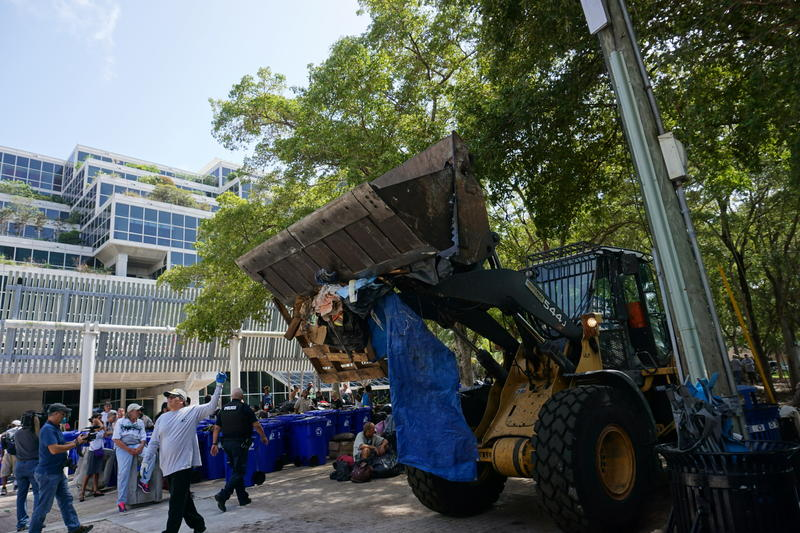 Fort Lauderdale workers throw away items from Stranahan Park.