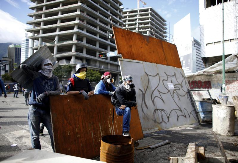 Anti-government demonstrators wait for Bolivarian National Guards at a barricade in Caracas, Venezuela, on Sunday.