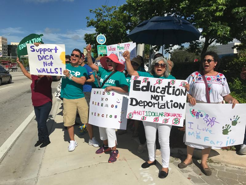 Ralliers hold signs calling for 'Education Not Deportation' and 'Support DACA Not Walls'