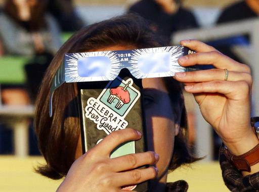 Catalina Gaitan, from Portland, Ore., tries to shoot a photo of the rising sun through her eclipse glasses at a gathering of eclipse viewers in Salem, Ore., Monday, Aug. 21, 2017.