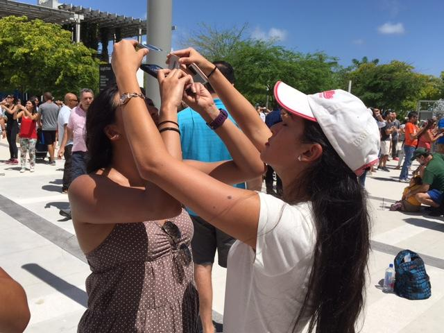 María José and María Dolores Betanga took turns using the protective glasses to look at the eclipse from outside the Frost Science Museum.