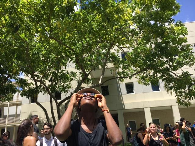 Hedrick Tussaint, a FIU alumnus, takes a moment to see the eclipse in the middle of his Monday.