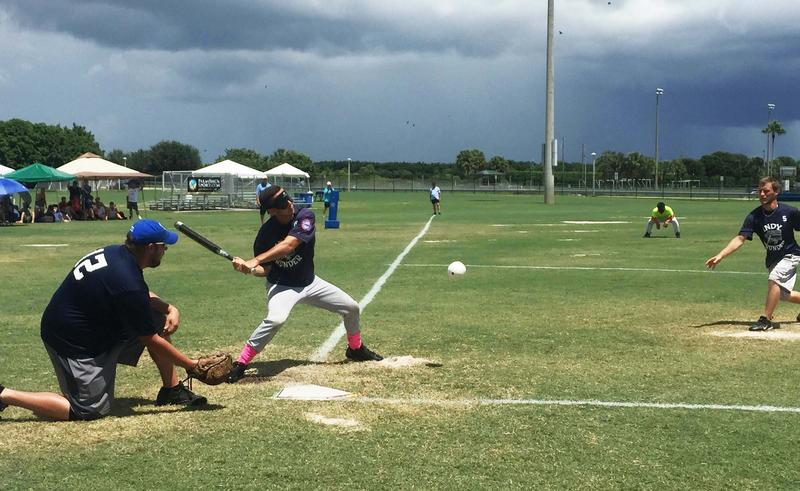 Storm clouds gather over the field as a player for the Indy Thunder takes a swing.