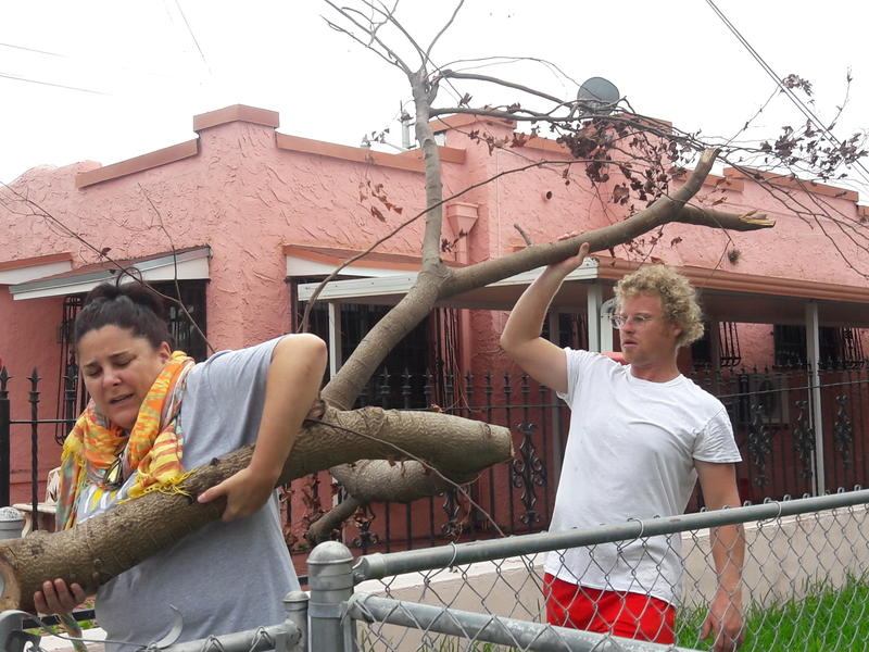 Volunteers with Koncious Contractors remove tree branches from a Little Havana home.