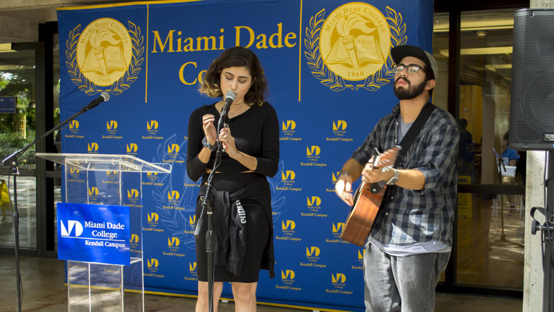 Lina Madory and Jonathan Diaz sing songs of peace and solidarity during a vigil held at Miami Dade College Kendall Campus
