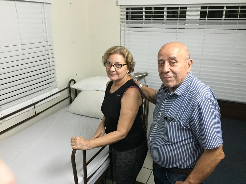 Dr. Hortencia Perez (left) and Dr. Manuel Herrero standing by one of the beds at their Santa Teresita nursing home in Rio Piedras, Puerto Rico.