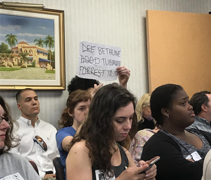 Woman holding sign at meeting