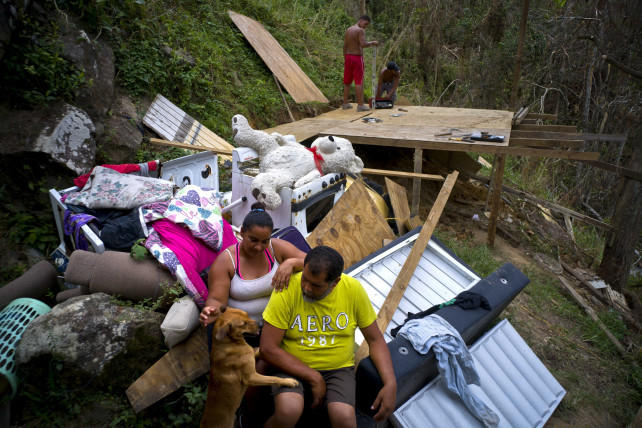 A family in Moravis, Puerto Rico, looks over the remains of their home destroyed by Hurricane Maria