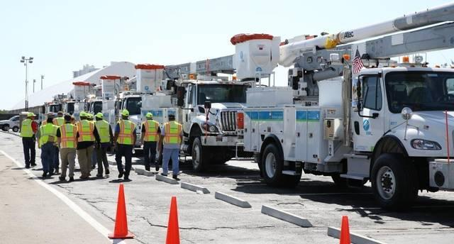 Utility workers head for their trucks during the aftermath of Hurricane Irma in South Florida.