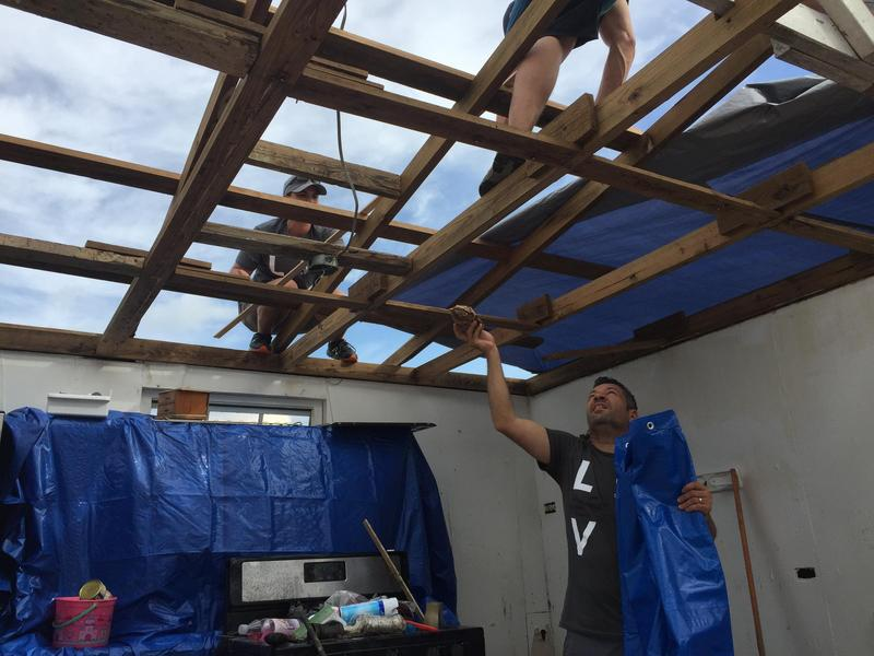 Puerto Rican volunteers from Florida place newly arrived tarps over hurricane-ravaged roofs in a barrio of Toa Baja.