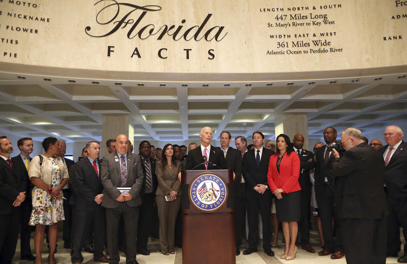 Gov. Rick Scott, center, addresses legislators and others at the end of special session, Friday, June 9, 2017, in Tallahassee, Fla.