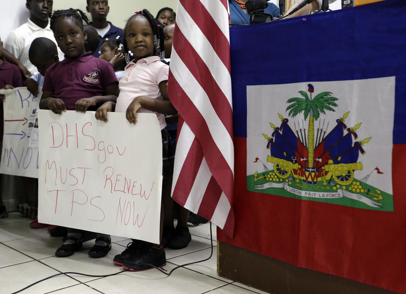 Children stand next to U.S. and Haitian flags as they hold signs in support of renewing Temporary Protected Status for immigrants from Central America and Haiti, during a news conference Monday, Nov. 6, 2017, in Miami.