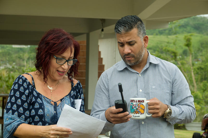 Mc Nelly Torres (left) shows Eliezer Maldonado, editor of La Cordillera newspaper in Puerto Rico, how to use a satellite phone for reporting.