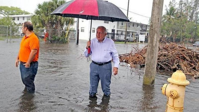 Miami Mayor Tomas Regalado holds an umbrella in an area of Shorecrest where the October king tides caused severe flooding. Voters passed the mayor's $400 million Miami Forever bond Tuesday, nearly half of which will pay to brace the city against sea rise.