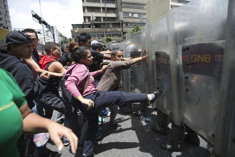 Venezuelans lash out at  National Guard troops during Caracas street protests last year against chronic food shortages.