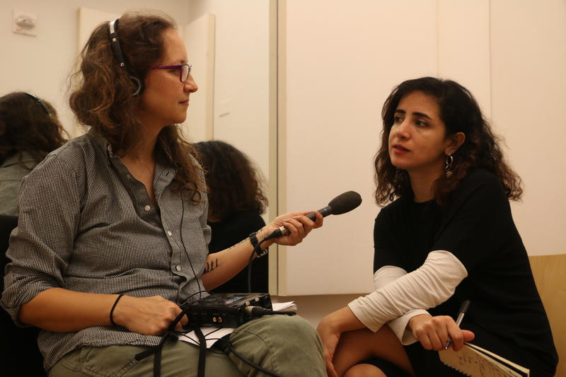 """Artist Tania El Khoury (right) during her conversation with Alicia Zuckerman.  Zuckerman's arm bears a depiction of a refugee journey, drawn on her arm during El Khoury's """"As Far As My Fingertips Take Me."""""""