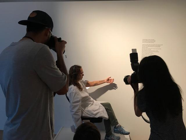 """""""As Far As My Fingertips Take Me"""" is presented to just one person at a time, listening on headphones to the story of a refugee, while an artist paints a journey on your arm."""
