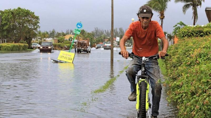 A man bikes through the flooding in the streets of Sweetwater in October. Cities that wait to address the effects of climate change, like sea level rise, could pay more in bonds when they get around to it.