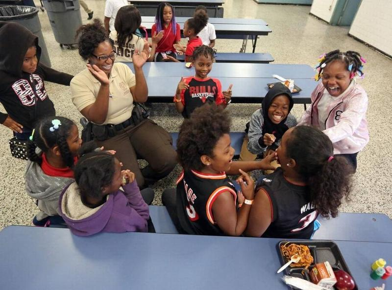 In this photo from May, third graders at Ponciana Park Elementary School eat lunch with a visiting police officer. The school near Liberty City will soon have another tenant: a privately run charter school.