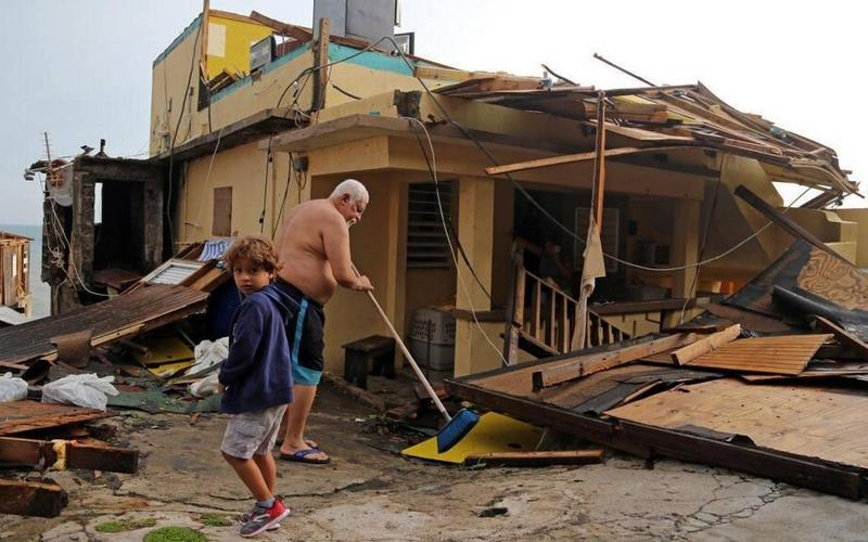 Residents of San Juan's La Perla neighborhood deal with the task of cleaning up after Hurricane Maria.