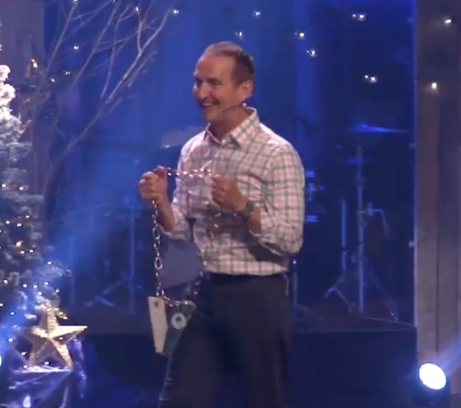 "Pastor Rick Blackwood holds a ""Volunteer Chain"" modeled after University of Miami's turnover chain."