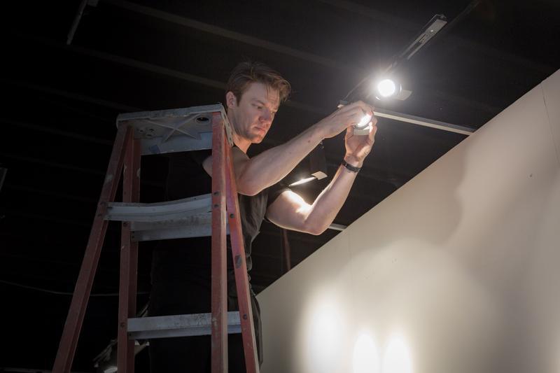 Charles Selander adjusting the lights at the Superfine Art Fair in Midtown Miami.