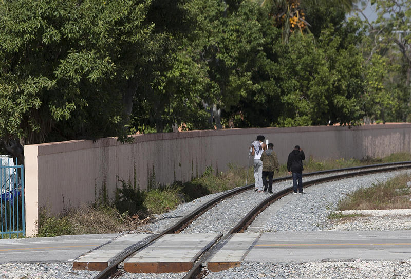 People crossing the rails nearby a Brightline station. CREDIT AP PHOTO/WILFREDO LEE