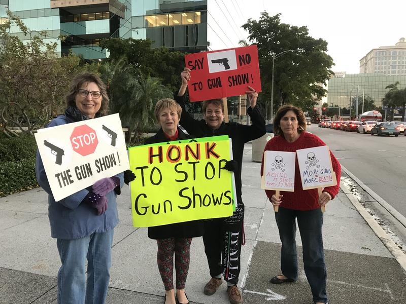 women standing with signs to end gun shows