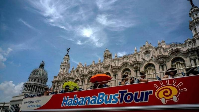 Tourists ride a tour bus in front of the Capitolio in Havana, Cuba, in June 2017.