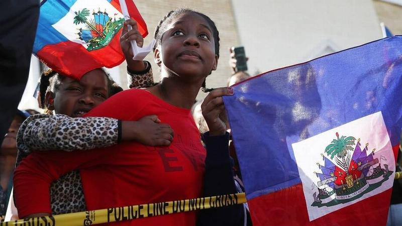 """Protesters gather at President Trump's Mar-a-Lago resort on Monday, Jan. 15, in response to reports that the president called Haiti, Africa and El Salvador """"shithole countries."""""""