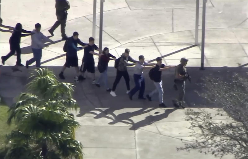 Students are being led out of the Marjory Stoneman Douglas High School in Parkland by members of the SWAT team.