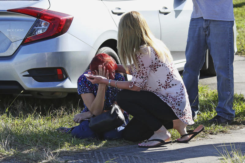 A woman consoles another as parents wait for news regarding a shooting at Marjory Stoneman Douglas High School in Parkland, Fla.